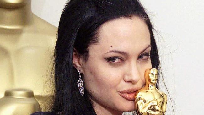 Angelina Jolie holding her Academy Award.