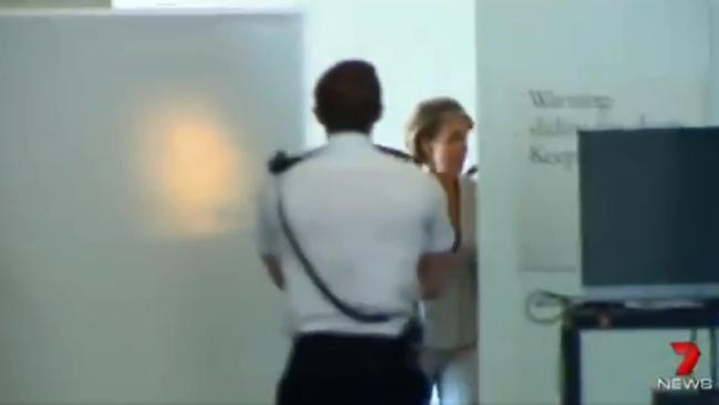 Jobs Minister Michaelia Cash hides behind a white screen on her way to Senate estimates.