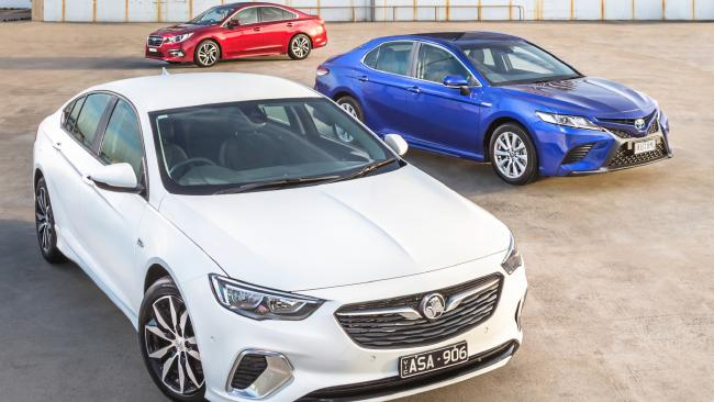 The German Holden Commodore four-cylinder takes on the all-new Toyota Camry Hybrid and updated Subaru Liberty. Picture: Thomas Wielecki.