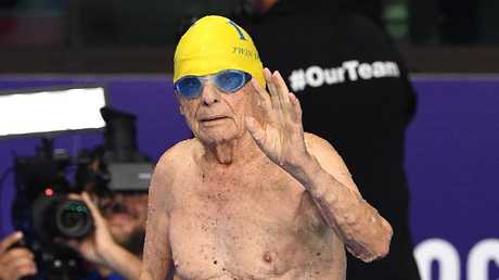 99-year-old George Corones waves to the crowd after breaking the 100m freestyle world record in the 100 — 104 year age group Saturday.