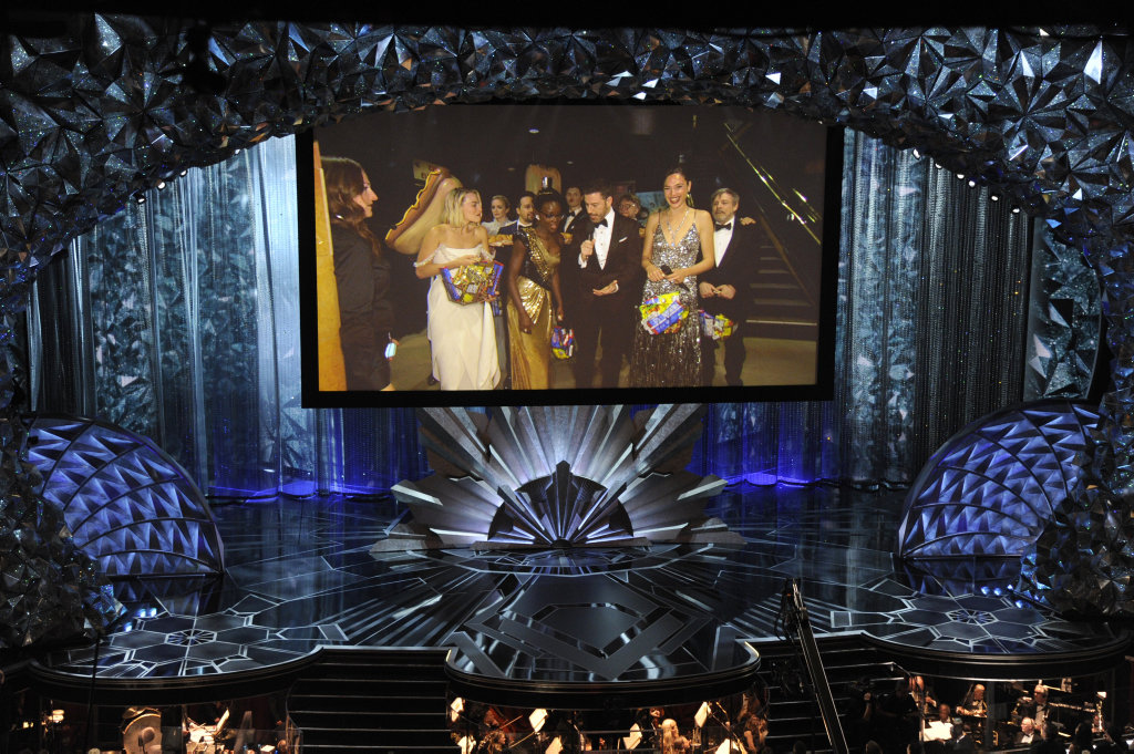 Margot Robbie, from left, Lupita Nyong'o, host Jimmy Kimmel, Gal Gadot, and others appear on screen via satellite at the Oscars on Sunday, March 4, 2018, at the Dolby Theatre in Los Angeles.