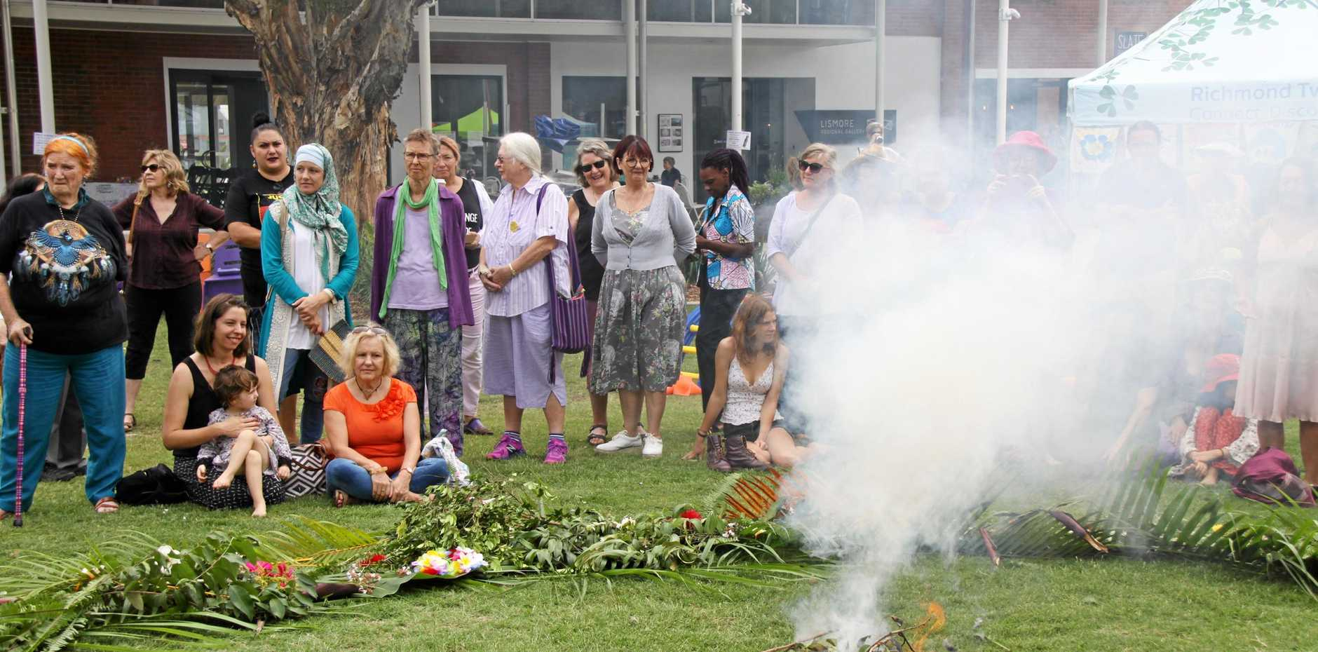 LISMORE WOMEN'S FESTIVAL: Around 100 people attended the opening of the LWF at the Quad on Saturday morning which included a Welcome to County, where everyone was invited to place a flower or foliage on the fire in memory of someone special..