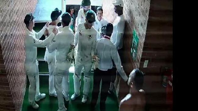 David Warner is held back by teammates in an argument with Quinton de Kock