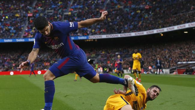 FC Barcelona's Luis Suarez, left, duels for the ball against Atletico Madrid's Koke