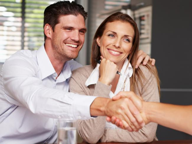 A young couple meeting with their mortgage broker after making a property purchase.
