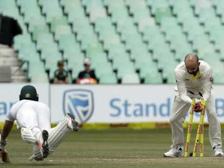 Australia's bowler Nathan Lyon, right, reacts after running out South Africa's batsman AB de Villiers, for a duck.