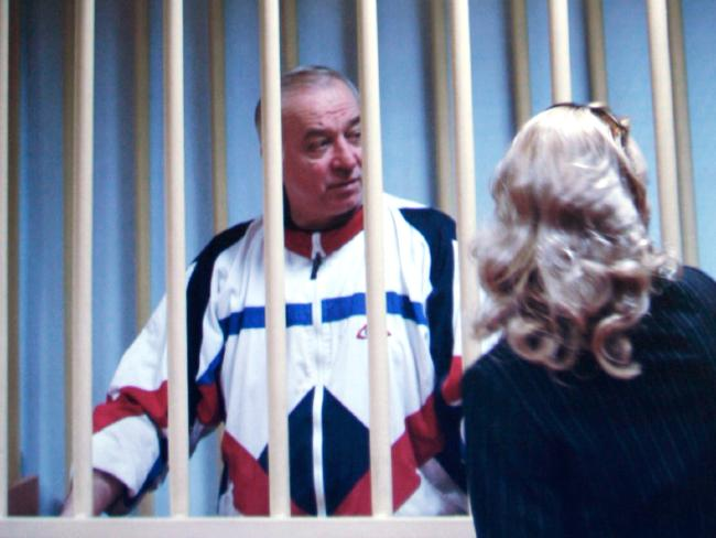 Sergei Skripal speaks to his lawyer from behind bars seen on a screen of a monitor outside a courtroom in Moscow, taken in 2006. Picture: AP/Misha Japaridze