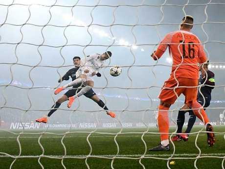 Real Madrid's Portuguese forward Cristiano Ronaldo heads the ball and scores