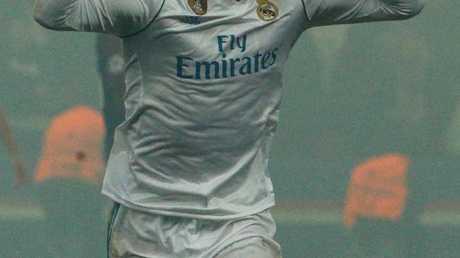 Real Madrid's Portuguese forward Cristiano Ronaldo celebrates amidst a haze.
