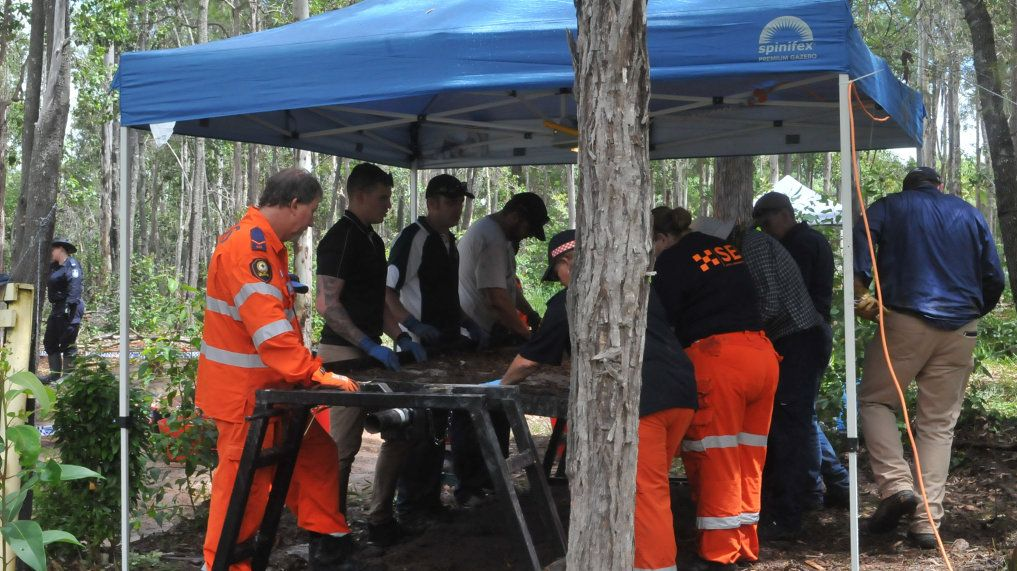 Police and SES crews search for clues at the site of a gruesome death at Goomboorian.