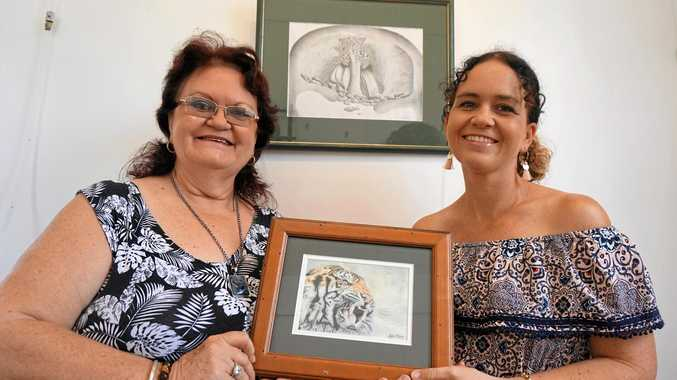 Dianne Moran and her daughter Jodie Perna with artwork which will be on display at the annual Sarina 7 exhibition at the Sarina Art Gallery. Jodie is holding a tiger, her final transformation of the looks of doomed pop superstar Michael Jackson.