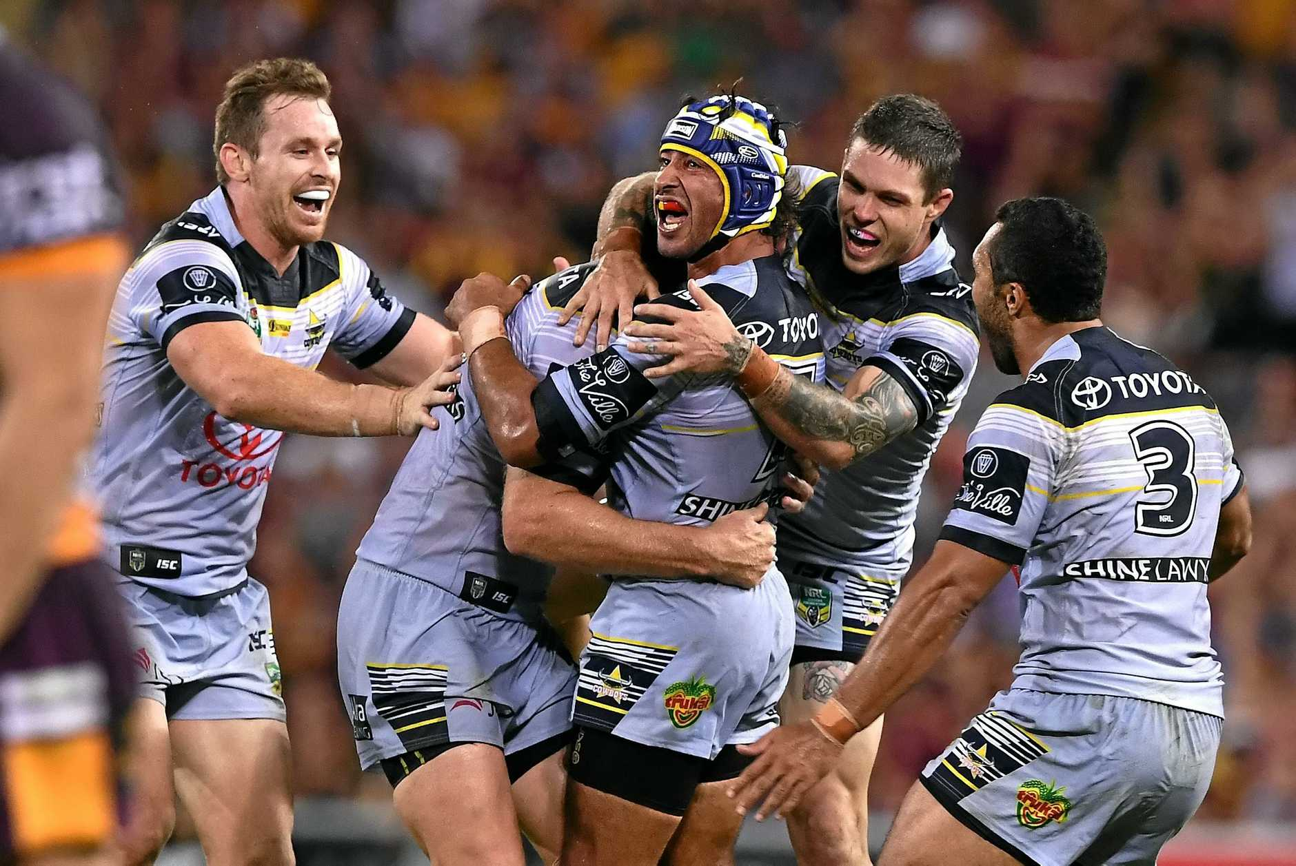 Johnathan Thurston is swamped by teammates after a match-winning play.