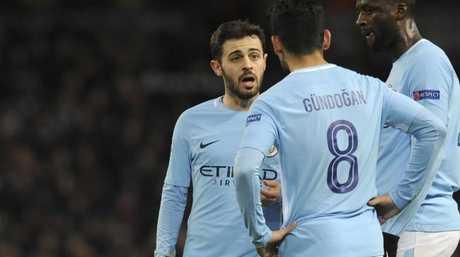 Manchester City's Bernardo Silva, left, speaks with Ilkay Gundogan, center, and Yaya Toure