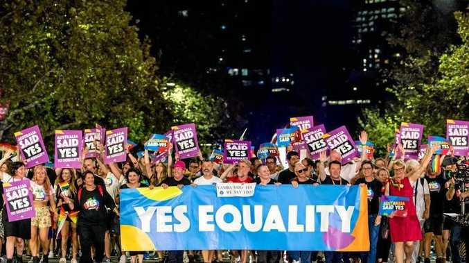 WE SAY 'I DO': Yamba residents Graeme East and Dean Valerio (centre) hold the banner for Marriage Equality at the 40th Mardi Gras in Sydney a small banner that says: 'Yamba said yes, we say I do'.