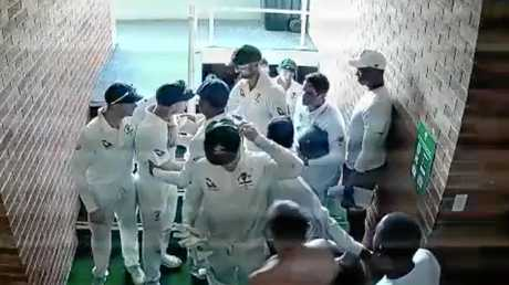 David Warner is held back by teammates.
