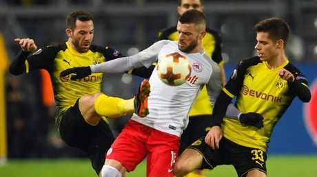 Salzburg's Valon Berisha and Dortmund's Julian Weigl and Gonzalo Castro vie for the ball.