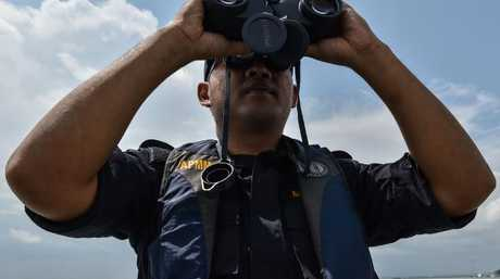 A member of the Malaysian Maritime Enforcement Agency officer uses a pair of binoculars to scan the sea during the rescue operation for the missing sailors from the USS John S. McCain off the Johor coast of Malaysia on August 24, 2017. Picture: AFP Photo / Mohd Rasfan