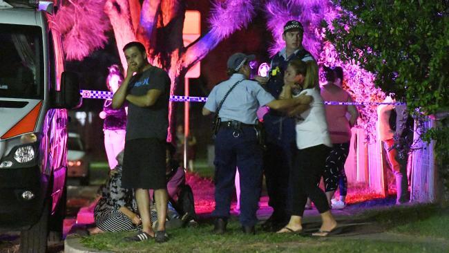 Police comfort people at the scene in Dharruk. Picture: Gordon McComiskie