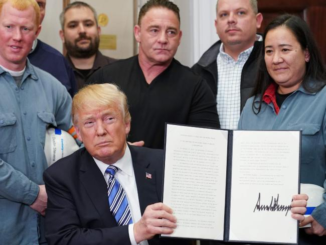 US President Donald Trump shows his signature on Section 232 Proclamations on Steel and Aluminum Imports. Picture: AFP