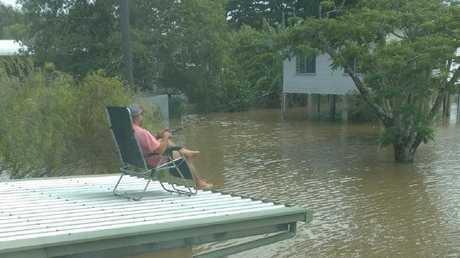 Ingham resident Tony Godfrey fishing for barra off his roof.