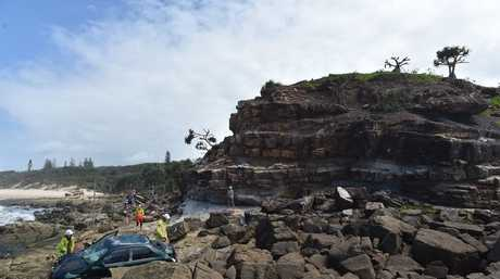 SCENE: A car has crashed through a fence and over the cliff at Point Arkwright.
