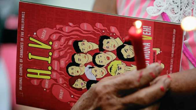 A Filipino woman holds on to an informational book on HIV/AIDS during a candle lighting event on World AIDS Day.