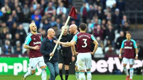 West Ham United's Welsh defender James Collins (2R) confronts a pitch invader carrying a corner flag