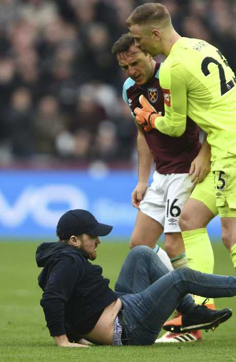 A Pitch invader falls to the pitch confronted by West Ham's Mark Noble, with goalkeeper Joe Hart, right.