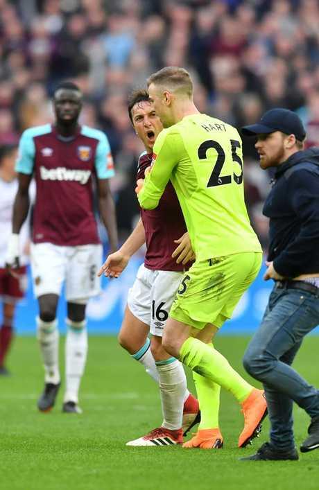 West Ham United's English goalkeeper Joe Hart (C) intercedes between West Ham United's English midfielder Mark Noble (L) and a 'fan'