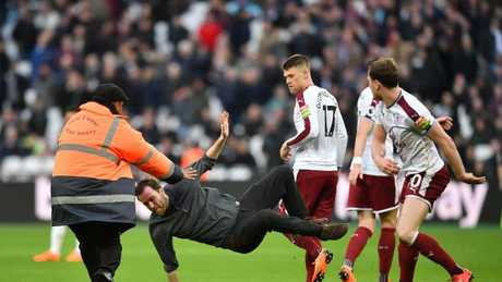 Burnley's English striker Ashley Barnes trips up a pitch invader.