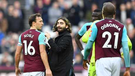 A pitch invader (2L) confronts West Ham United's English midfielder Mark Noble (L)