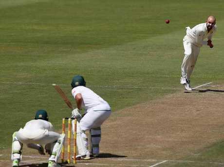 Australia's Nathan Lyon delivers the ball to South Africa batsman Dean Elgar.