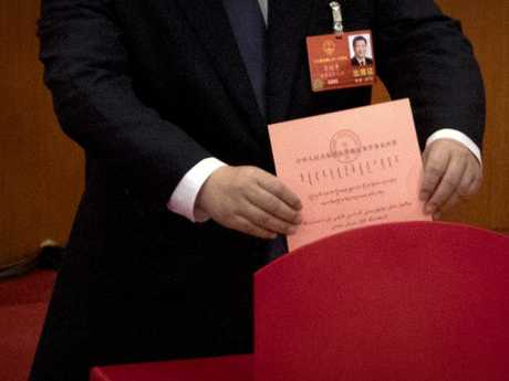 Xi Jinping places his ballot in a ballot box during a plenary session of China's National People's Congress. Picture: AP/Mark Schiefelbein