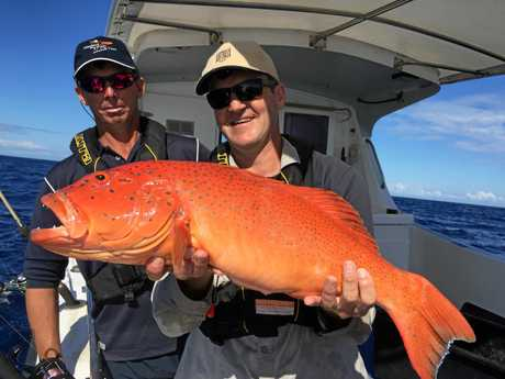 Fishing Australia host Rob Paxevanos pictured with a coral trout and 1770 charter fishing operator Damien Robeck.