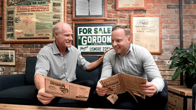 R Gordon and Son team Andrew Gordon and Nathan Gordon study old newspaper ads for the business which has seen five generations of the Gordon family work and operate out of the same office building in Lismore.