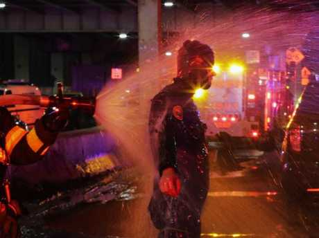 A FDNY diver is sprayed with water after attending a call of a helicopter crash in the East River. Picture: Getty