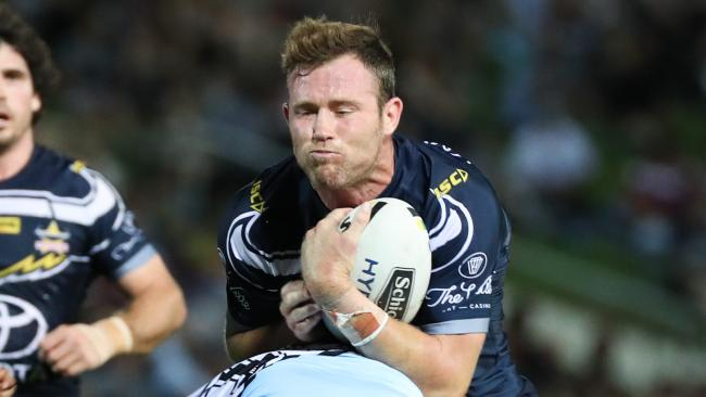 Gavin Cooper of the Cowboys is tackled by Sharks players.