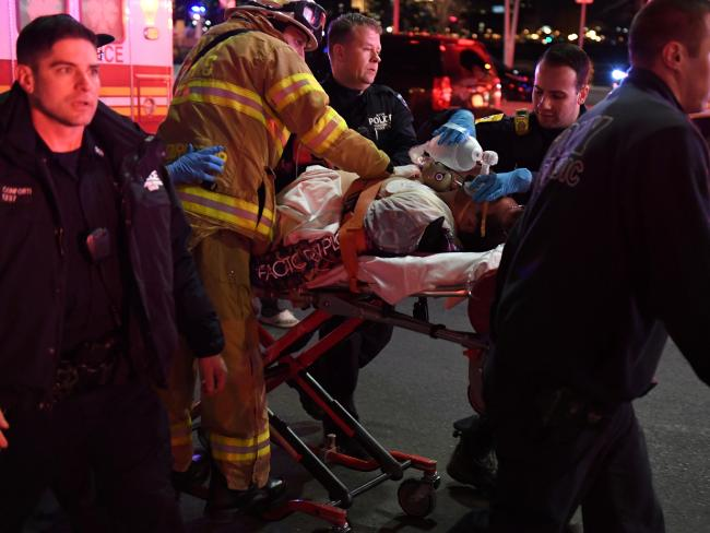 Paramedics and members of the FDNY perform CPR on a victim of a helicopter that crashed into the East River. Picture: Reuters