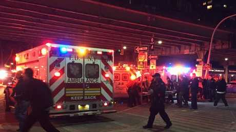 First responders carry a person to an ambulance after a helicopter crashed into the East River along New York. Picture: AP