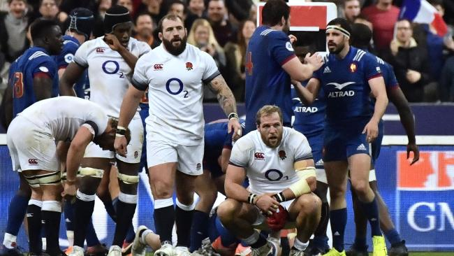England's players react as France's players celebrate their Six Nations win in Paris.