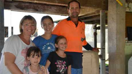 Luke Chittenden with his wife Tiffany and children Brydie (middle), Jorja (left) and Lily (right), mark where the water came up under their house. Picture: Chris Lees