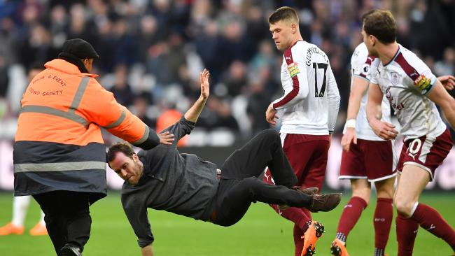 Burnley's English striker Ashley Barnes trips up a pitch invader