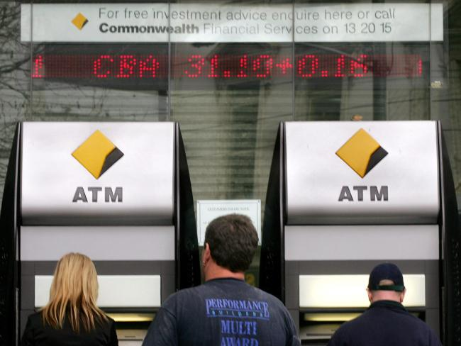 Customers use automatic teller machines (ATM) outside a branch of Commonwealth Bank of Australia (CBA). Picture: AFP