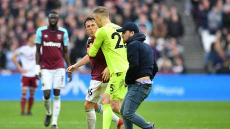 West Ham United's English goalkeeper Joe Hart (C) intercedes between West Ham  Mark Noble (L) and a pitch invader (R)
