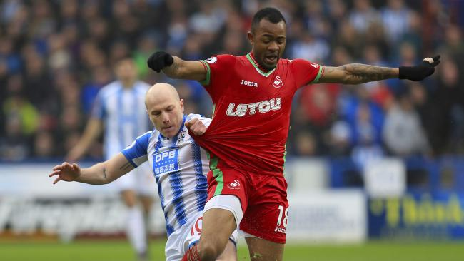 Huddersfield Town's Aaron Mooy, left, and Swansea City's Jordan Ayew