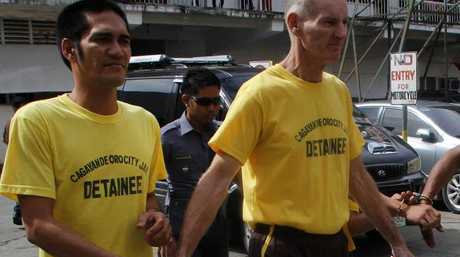 Peter Scully of Australia (right), accused of raping and trafficking two girls in the Philippines, leaves court handcuffed to another inmate after his arraignment. Picture: AFP