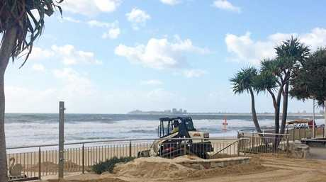 A BOBCAT removes sand from the Maroochydore Beach car park as Cyclone Linda begins to make an impact on the Sunshine Coast.
