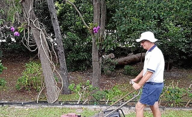 It's business as usual for Fraser Island's David Anderson as he mows his lawn while Cyclone Linda brews off the coast.