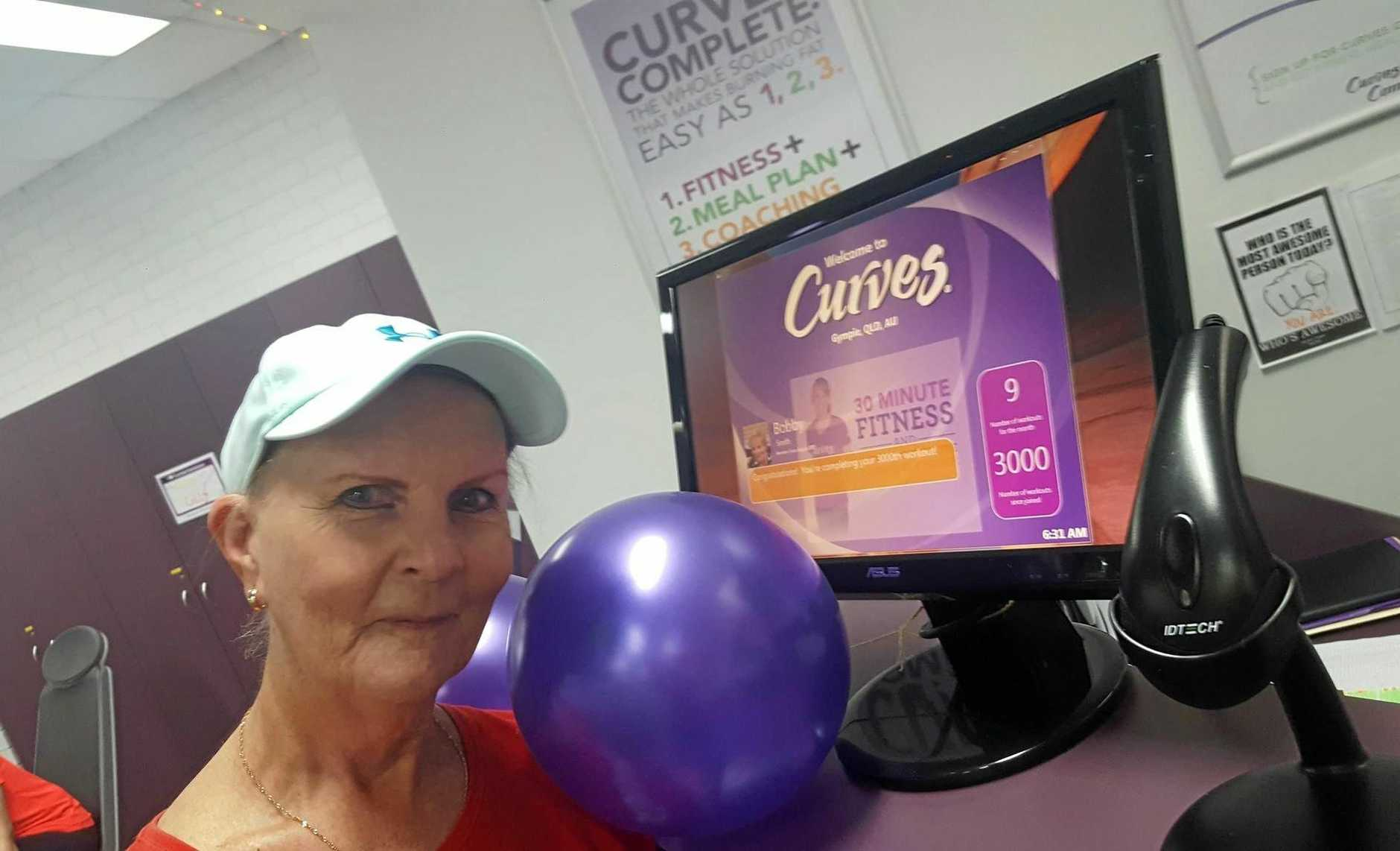 HIGH ACHIEVER: Bobby poses at Curves with the official online recognition of her milestone workout.