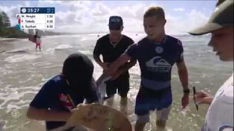 Gold Coast surfer Mick Fanning hands his surfboard to a young fan after being eliminated from the Quiksilver Pro, Gold Coast.